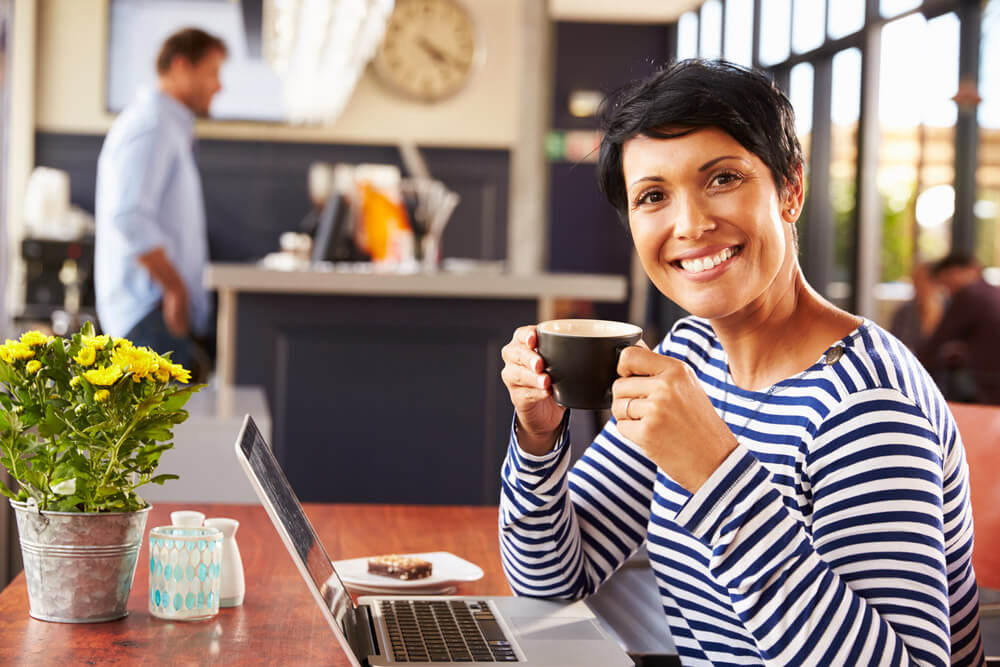 Woman enjoying a mug of coffee at a coffee house