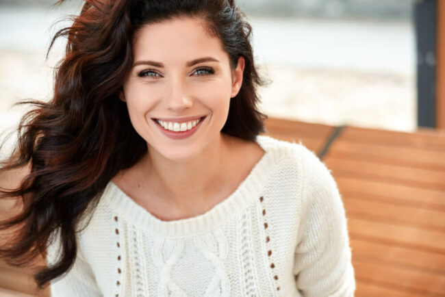 Happy, smiling woman in white sweater