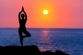 Girl with Glaucoma doing Yoga at the beach while the sun is setting