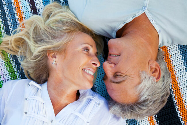 Older couple on beach blanket looking at each other