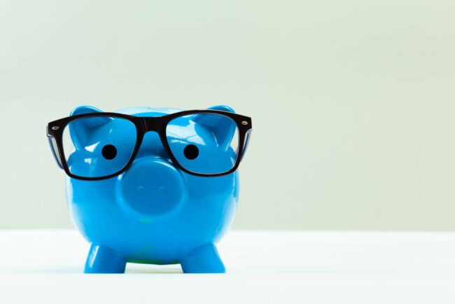 Blue piggy bank wearing glasses