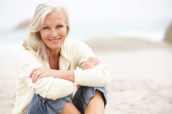 Older woman sitting on beach and smiling
