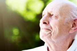 Old man with eye trouble squints up at sun