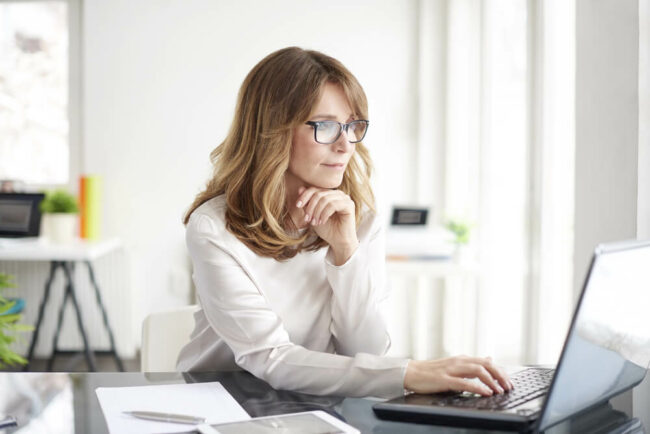 Middle-aged woman wearing glasses and looking at computer