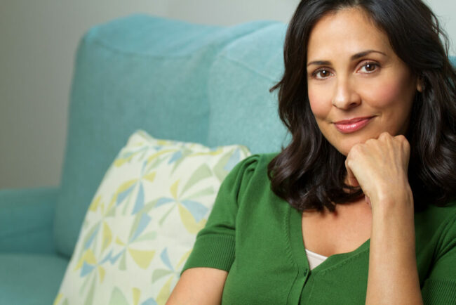 Middle-aged woman sitting on couch with hand on chin
